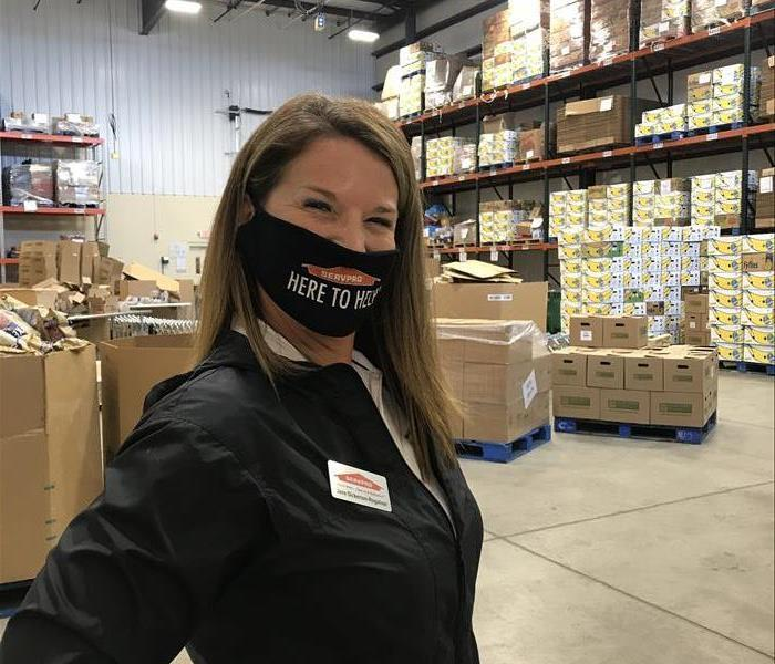 female employee with here to help mask standing in warehouse