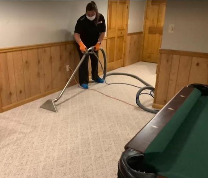 crew member extracting water from carpet in residential home