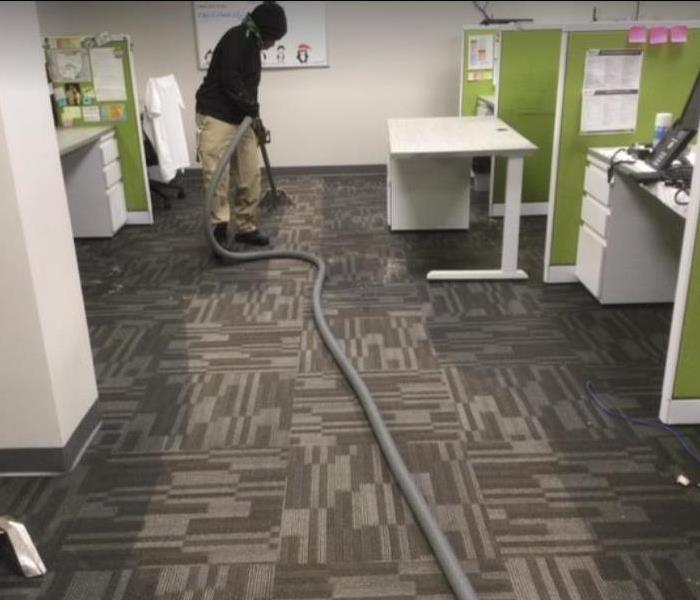 technician extracting water from carpet